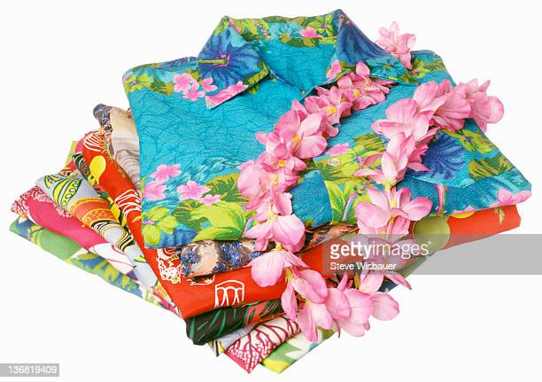 A stack of folded Hawaiian shirts with a lei