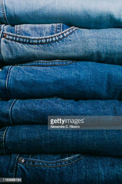 stack of folded jeans - jeans stock pictures, royalty-free photos & images