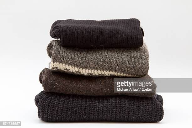 Stack Of Folded Sweaters Against White Background