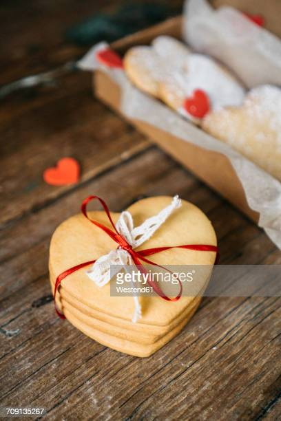 Stack of four heart-shaped shortbreads tied with lace and ribbon on wood