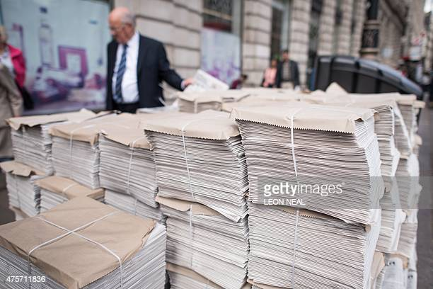 Stack of free newspapers are shown in a central London street. AFP PHOTO / LEON NEAL