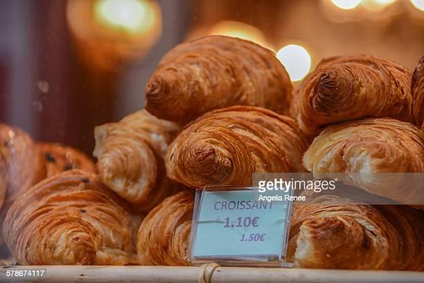 Stack of golden croissants in bakery window