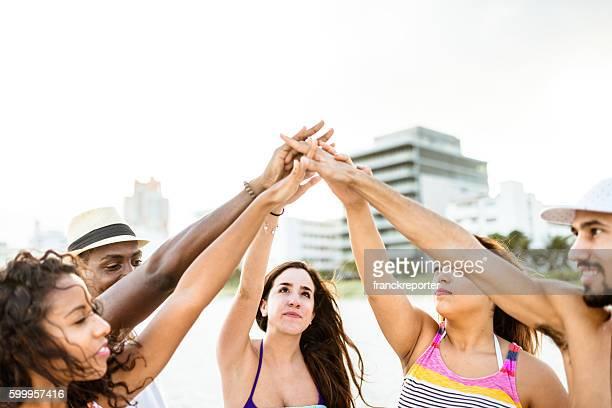 Ein Haufen Hände Zusammenhalt für teamwork am Strand