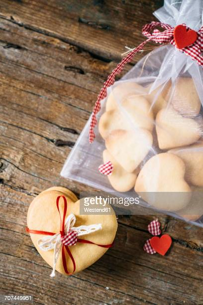 Stack of heart-shaped shortbreads tied with lace and ribbon and sachet with shortbreads on wood