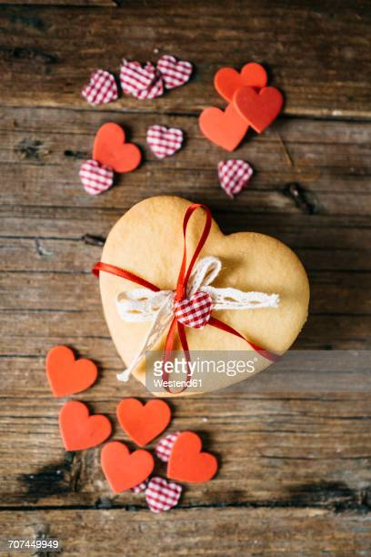Stack of heart-shaped shortbreads tied with lace and ribbon on wood