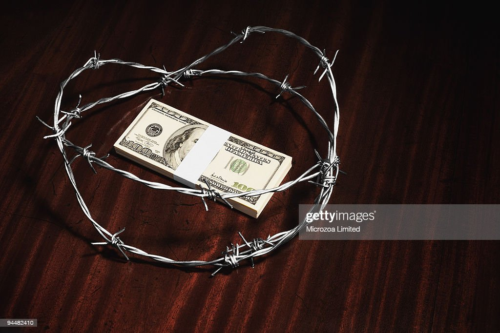 Stack of hundred dollar bills surrounded by barbed wire : Stock Photo