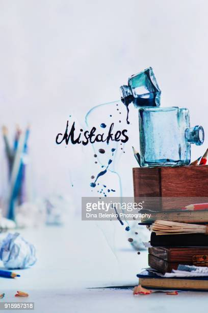 Stack of inkwells and pencils boxes with spilling ink forming word Mistakes. Creative writing concept in high key. Dynamic shot with frozen motion.