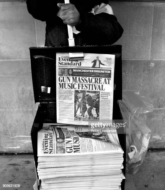 Stack of London Evening Standard newspapers being distributed at a street corner in London, England. The headline refers to a mass murder the...