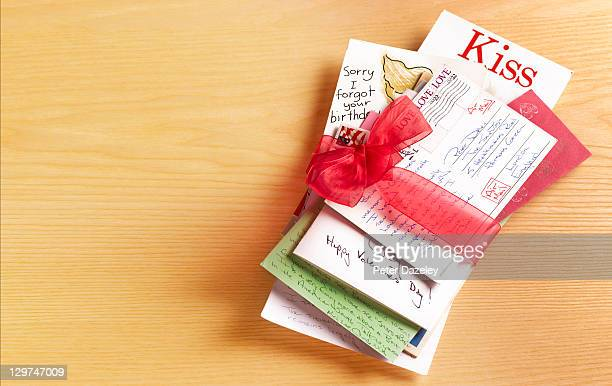 stack of love letters tied with red ribbon - love letter stock photos and pictures