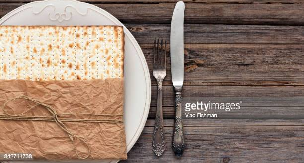 Stack of matzah or matza with a white plate and silverware on a vintage wood background presented as a gift with copy space