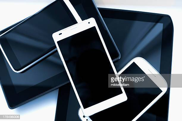 Stack of mobile phones and tablets on a white background