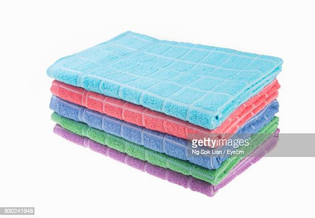 Stack Of Multi Colored Folded Towels Over White Background