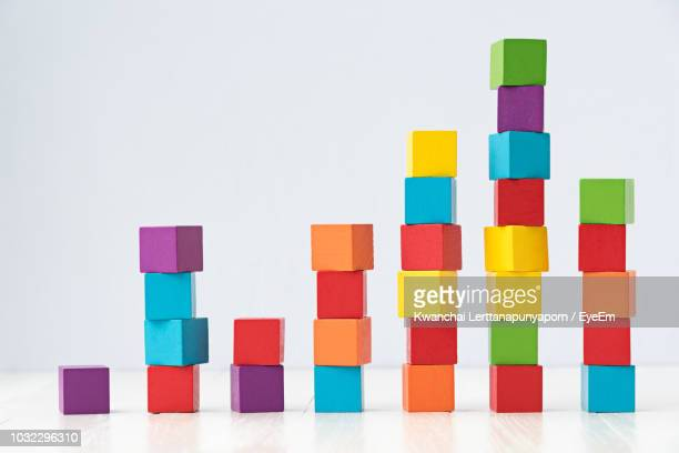 stack of multi colored toy blocks against white background - bar graph stock pictures, royalty-free photos & images
