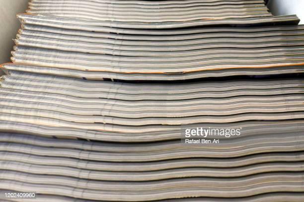 stack of newspapers layers in magazines rack - rafael ben ari fotografías e imágenes de stock