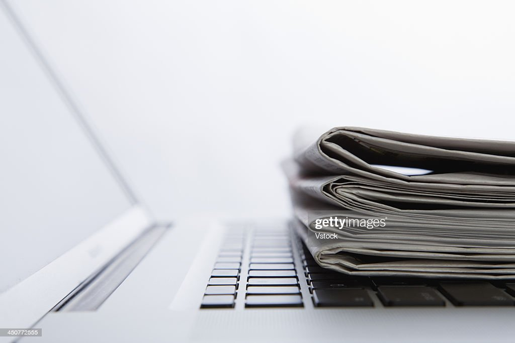 Stack of newspapers on laptop. close-up : Stock Photo