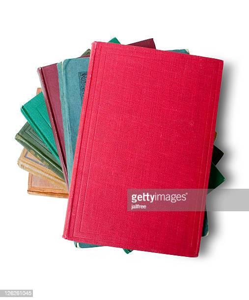 La pila de viejos libros con libro rojo sobre blanco
