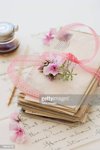 Stack of old letters next to flowers and ink bottle