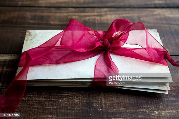 Stack of old love letters tied with red ribbon
