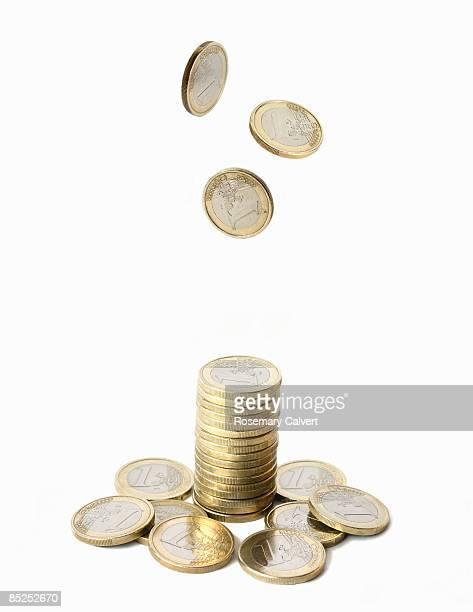 stack of one euro coins with coins falling above. - geldmünze stock-fotos und bilder