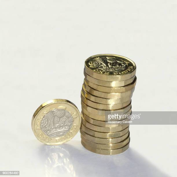 Stack of one pound coins with one coin on its edge.