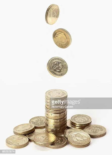 stack of one pound coins with pound coins falling  - stack stock pictures, royalty-free photos & images