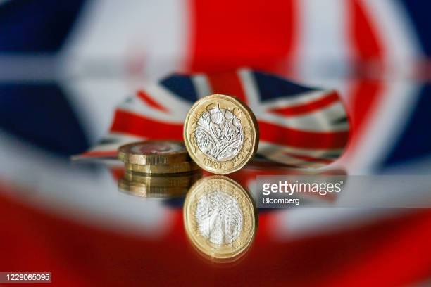 Stack of one pound sterling coins sit in front of a British Union flag, also known as a Union Jack, in this arranged photograph in London, U.K., on...