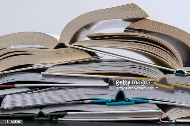 stack of open books on table - textbook stock pictures, royalty-free photos & images