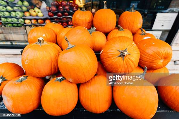 Stack of orange pumpkins on a stall at the farmer's market
