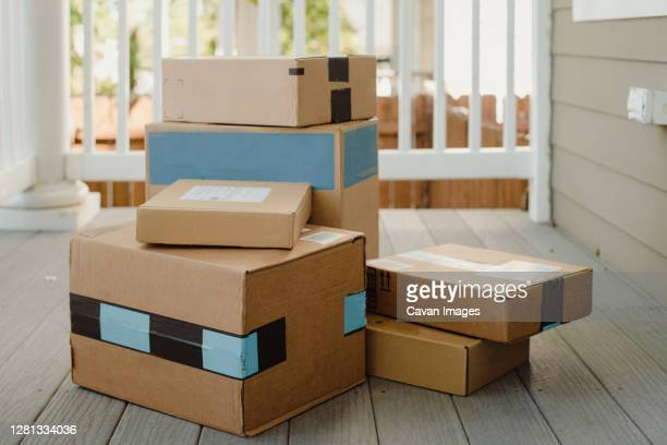 stack of packages on front porch after mail delivery - stack stock pictures, royalty-free photos & images