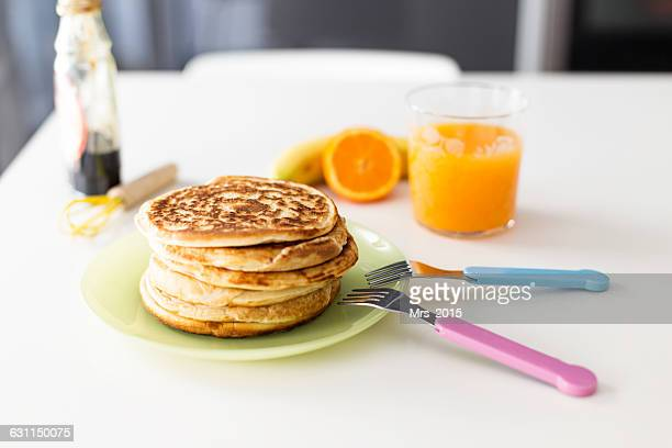 Stack of Pancakes and orange juice on table