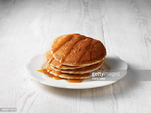 Stack of pancakes drizzled with butterscotch sauce