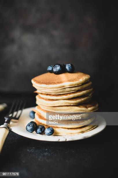 Stack of pancakes with blueberies on dark background