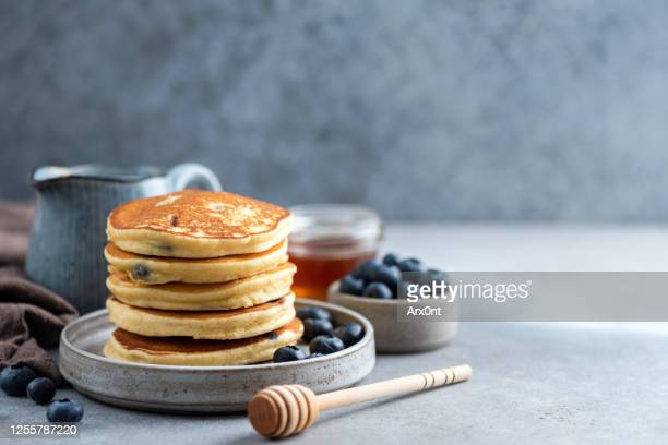 stack of pancakes with blueberries and honey - pancakes stock pictures, royalty-free photos & images
