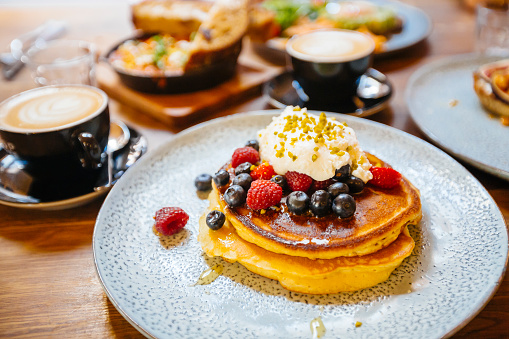 Stack of pancakes with fresh blueberry, raspberry and ricotta cheese on a plate, served with coffee in cafe - gettyimageskorea