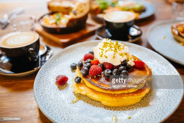 stack of pancakes with fresh blueberry, raspberry and ricotta cheese on a plate, served with coffee in cafe - スイーツ ストックフォトと画像