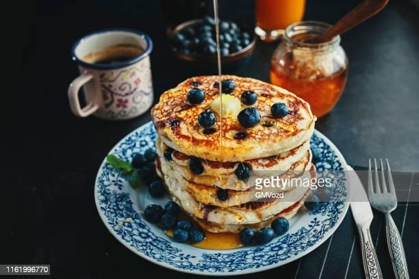 pilha de panquecas com xarope de bordo e blueberries frescas - comida pronta - fotografias e filmes do acervo