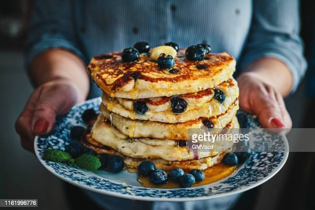 stack of pancakes with maple syrup and fresh blueberries - pancake stock pictures, royalty-free photos & images
