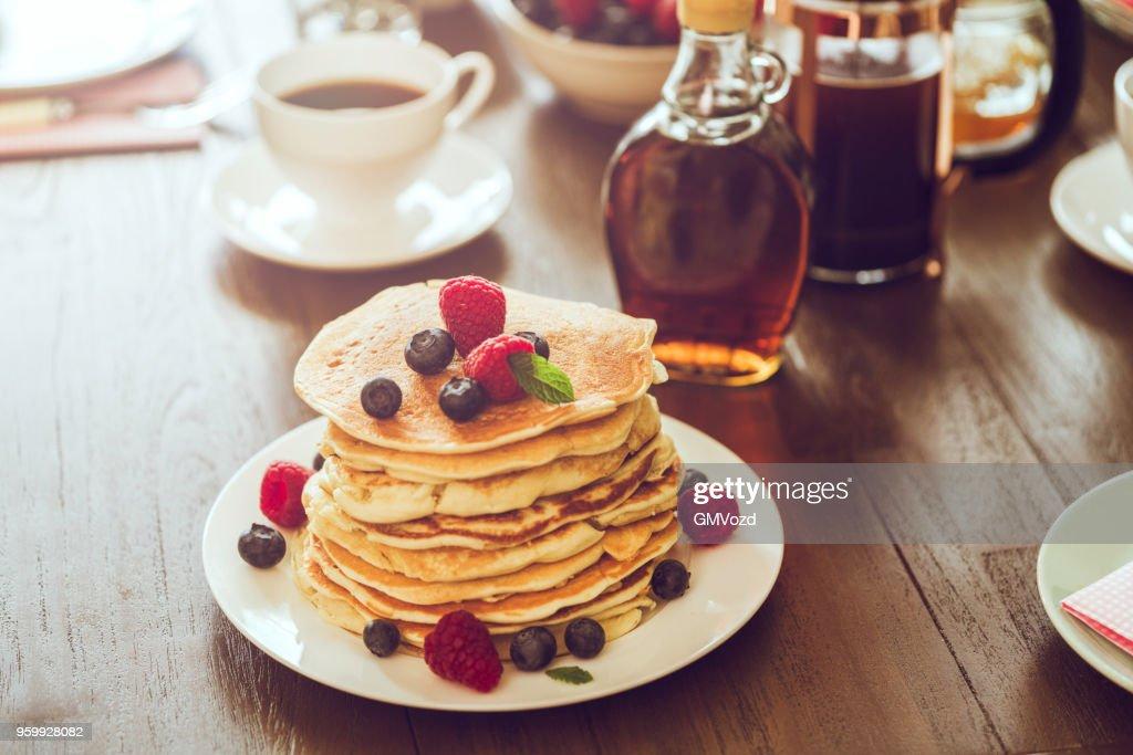 Stapel von Pfannkuchen mit Ahornsirup, Beeren und frischen Kaffee : Stock-Foto