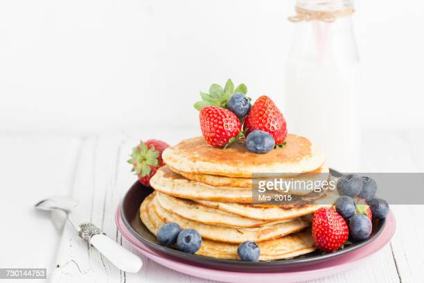 Stack of pancakes with maple syrup, fresh strawberries and blueberries