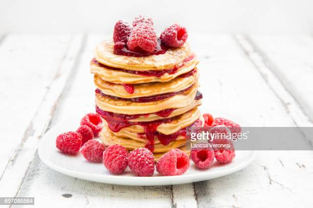 Stack of pancakes with raspberry sauce and raspberries