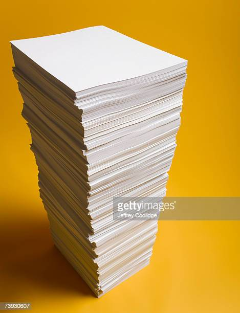 Stack of paper, yellow background, studio shot, elevated view