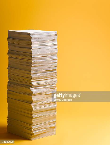stack of paper, yellow background, studio shot - catasta foto e immagini stock