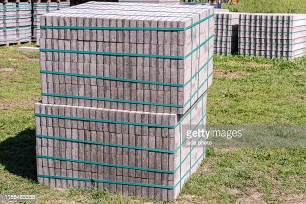 stack of paving stones stand on a lawn - 石造りの家 ストックフォトと画像