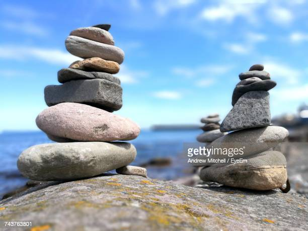 Stack Of Pebbles In Sea Against Sky