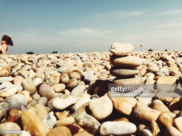 stack of pebbles on beach against sky - aldeburgh stock photos and pictures