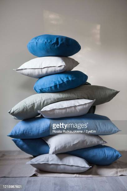stack of pillows against wall - cushion stock pictures, royalty-free photos & images