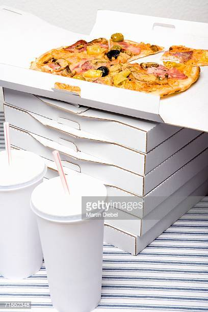 Stack of pizza boxes next to cups of soda