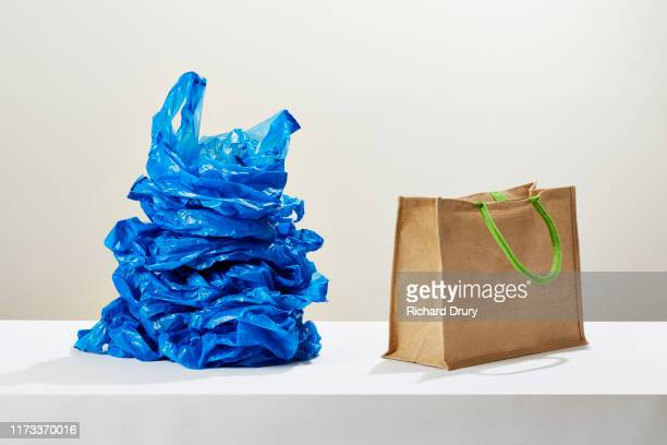 a stack of plastic carrier bags next to a reusable shopping bag - bag stock pictures, royalty-free photos & images