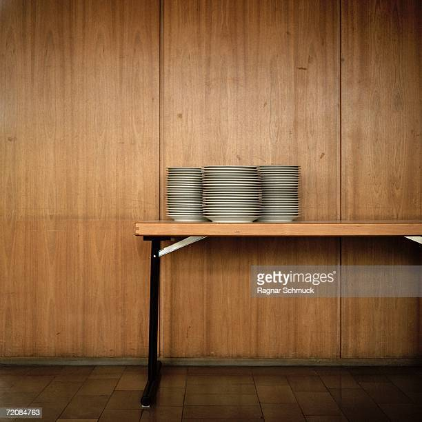 Stack of plates on table, in front of wood grain background