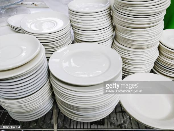 stack of plates on table in kitchen - abundance stock pictures, royalty-free photos & images
